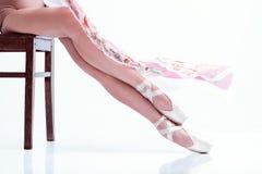 Los pies de la bailarina en pointe y con la bufanda de seda en el fondo blanco foto de archivo