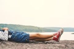 Los pies de la chica joven duermen en el parque en la naturaleza Imagen de archivo libre de regalías