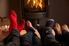 Los pies de la familia que se relajan por el fuego de registro acogedor Imagen de archivo libre de regalías