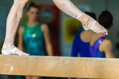 Los pies de la muchacha de los gimnastas ataron con correa el primer del haz Fotos de archivo libres de regalías