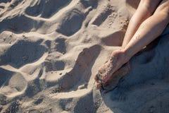 Los pies de la muchacha en la arena Imagen de archivo