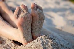 Los pies de la muchacha en la arena Imagenes de archivo
