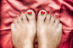 Los pies de la mujer de Beautifull en un satén rojo cubren foto de archivo