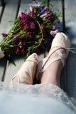 Los pies de la mujer en deslizadores del ballet con el dobladillo del cordón y un ramo próximo de wildflowers fotos de archivo