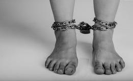 Los pies de la mujer fueron atados por el aislante de cadena en el fondo blanco Imágenes de archivo libres de regalías
