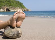 Los pies de la mujer que reclinan el coco varan, Costa Rica Imagenes de archivo