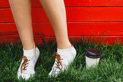 Los pies de la mujer que se colocan en hierba verde Imágenes de archivo libres de regalías