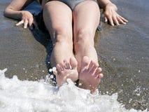 Los pies de la mujer que se relajan en la orilla que espera el mar hacen espuma Fotos de archivo libres de regalías