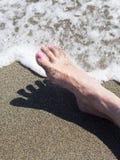 Los pies de la mujer que se relajan en la orilla que espera el mar hacen espuma Foto de archivo