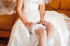 Los pies de la novia hermosa en zapatos y el blanco se visten Fotos de archivo libres de regalías