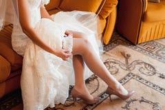 Los pies de la novia hermosa en zapatos y el blanco se visten Fotos de archivo