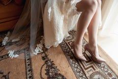 Los pies de la novia hermosa en zapatos y el blanco se visten Foto de archivo