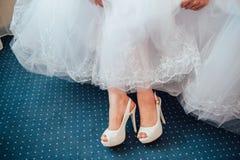 Los pies de la novia hermosa en zapatos y el blanco se visten Foto de archivo libre de regalías