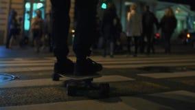 Los pies de la persona del skater montan a través de paso de peatones del camino de ciudad de la noche almacen de metraje de vídeo