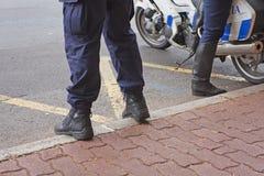 Los pies de la policía se colocan en la acera Fotografía de archivo