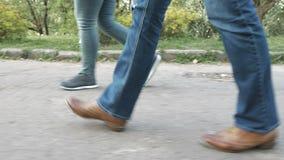Los pies de las mujeres en la acera en zapatos y zapatillas de deporte almacen de metraje de vídeo