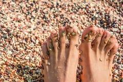 Los pies de las mujeres en la playa de los guijarros Imágenes de archivo libres de regalías