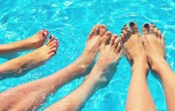 Los pies de las mujeres y de los hombres en la piscina Vacaciones en verano en tiempo claro imágenes de archivo libres de regalías