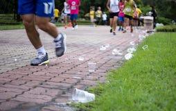 Los pies de los corredores de maratón y las tazas emptry del agua en el refresco señalan Imagen de archivo