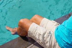 Los pies de los hombres en agua de la turquesa Fotografía de archivo libre de regalías