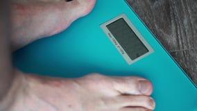 Los pies de los hombres en escala del peso almacen de metraje de vídeo