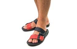 Los pies de los hombres en las sandalias de cuero Imagenes de archivo