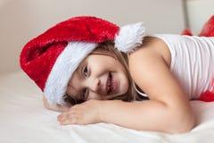 Los pies de los niños en las partes inferiores del pijama rayadas del Año Nuevo a la cama, Imagenes de archivo