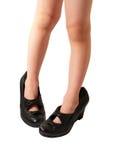 Los pies de los niños en los zapatos femeninos de cuero Imágenes de archivo libres de regalías
