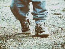 Los pies de los niños en pantalones y zapatillas de deporte de los deportes Imágenes de archivo libres de regalías