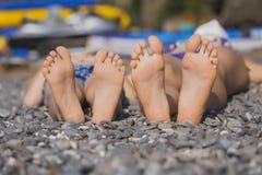 Los pies de los niños en hierba. Comida campestre de la familia Fotos de archivo