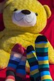 Los pies de los pares de la tarjeta del día de San Valentín con un peluche refieren el fondo Imágenes de archivo libres de regalías