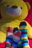 Los pies de los pares de la tarjeta del día de San Valentín con un peluche refieren el fondo Imagen de archivo libre de regalías