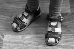 Los pies de los niños en sandalias del deporte en el suelo laminado fotos de archivo libres de regalías