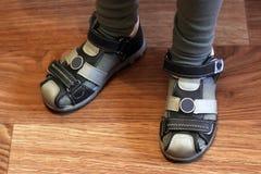 Los pies de los niños en sandalias del deporte en el suelo laminado fotos de archivo
