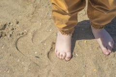 Los pies de los ni?os desnudos en la playa Primer imagenes de archivo