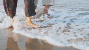 Los pies de los pares mayores que caminaban en la playa, steadicam tiraron almacen de metraje de vídeo