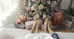 Los pies de los pares a través del árbol de navidad, del hombre y de la mujer se relajan los pies Cierre para arriba Días de fies almacen de video