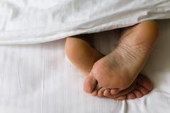 Los pies de piernas humanas resaltan de debajo la manta foto de archivo