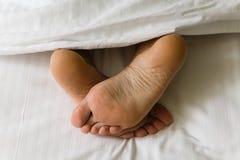 Los pies de piernas humanas resaltan de debajo la manta imagen de archivo libre de regalías