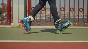 Los pies de los rollergirl expertos que hacen la posición cruzada metrajes