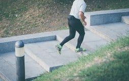 Los pies de viejo atleta de sexo masculino corren encima de las escaleras Imagen de archivo