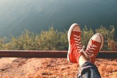 Los pies de zapatilla de deporte roja una muchacha en naturaleza y relajan tiempo Imagenes de archivo