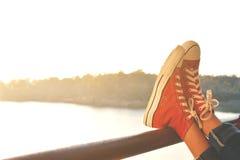 Los pies de zapatilla de deporte roja una muchacha en naturaleza y relajan tiempo Imagen de archivo