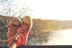 Los pies de zapatilla de deporte roja una muchacha en naturaleza y relajan tiempo Fotografía de archivo libre de regalías