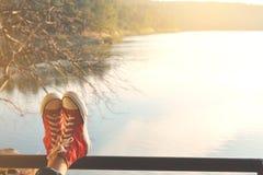 Los pies de zapatilla de deporte roja una muchacha en naturaleza y relajan tiempo Imágenes de archivo libres de regalías