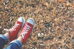 Los pies de zapatilla de deporte roja una muchacha en naturaleza y relajan tiempo Fotos de archivo libres de regalías