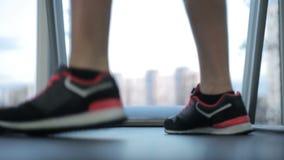Los pies del atleta de sexo femenino que caminan en la rueda de ardilla, mujer paran y acaban entrenamiento metrajes