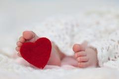 Los pies del bebé con la etiqueta del corazón del amor Imagen de archivo libre de regalías