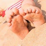 Los pies del niño cerca de la playa arenosa fotografía de archivo libre de regalías