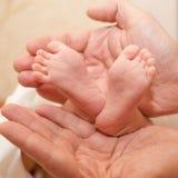 Los pies del bebé recién nacido en manos grandes Imagenes de archivo